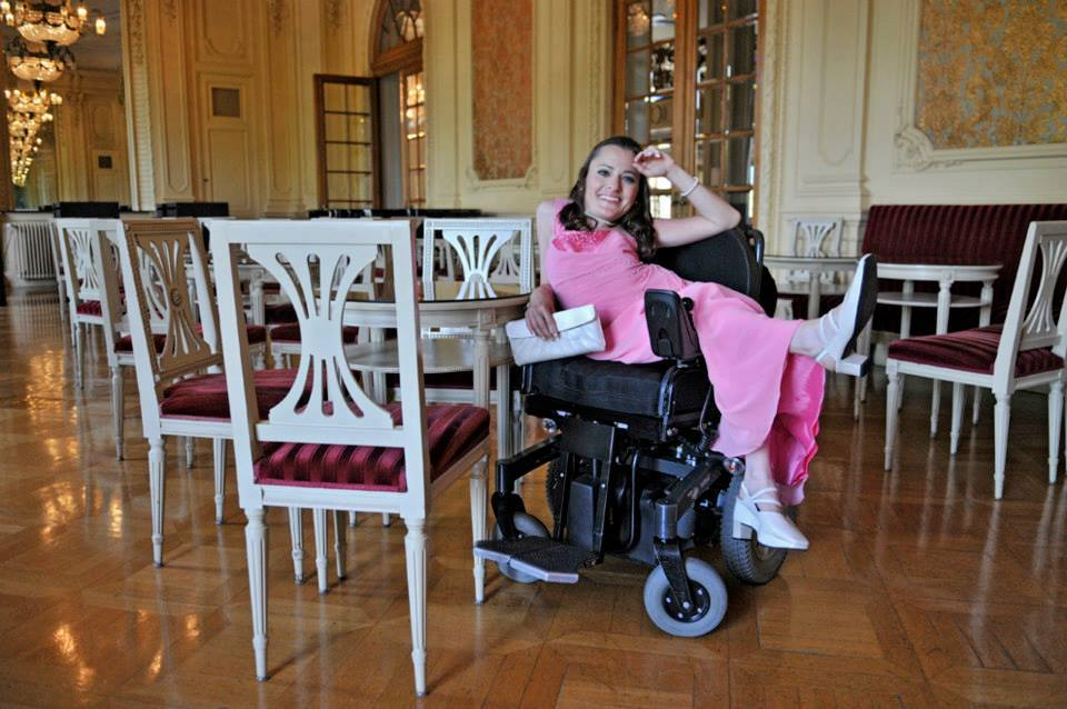 Jasmin Rechsteiner sitzt im Abendkleid über der Armlehne im elektrischen Rollstuhl