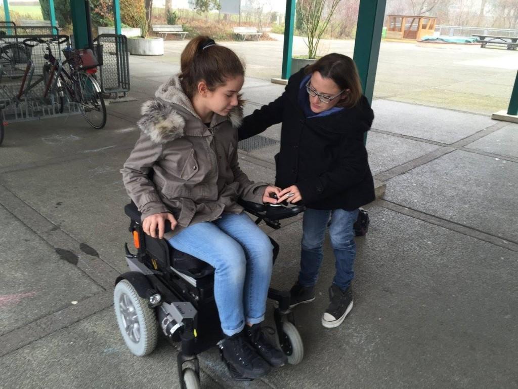 Eine Schülerin sitzt im elektrischen Rollstuhl von Jasmin Rechsteiner und Jasmin steht daneben und zeigt ihr, wie sie den Rollstuhl bedienen/fahren kann.